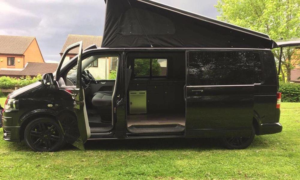 side profile of a black campervan with portfolio roof