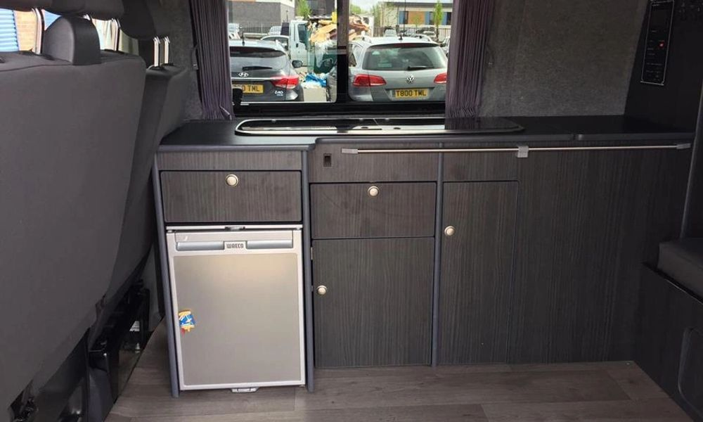 Kitchen area of campervan, including fridge and sink
