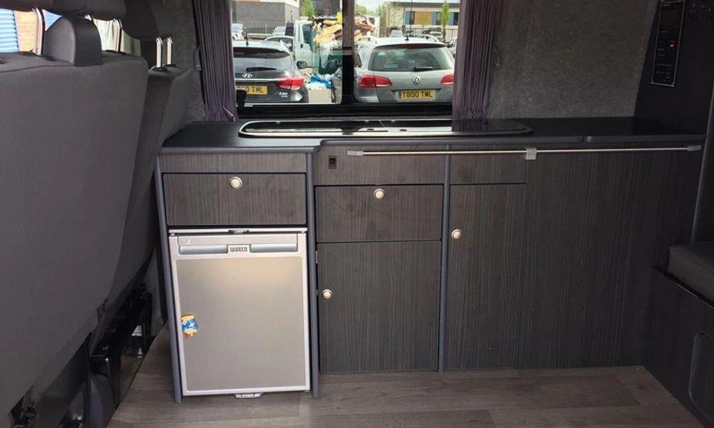 Kitchen area of campervan, including fridge and sink