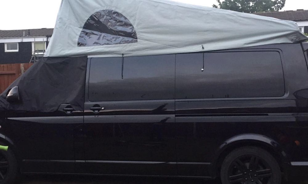 black vw campervan with portfolio roof area