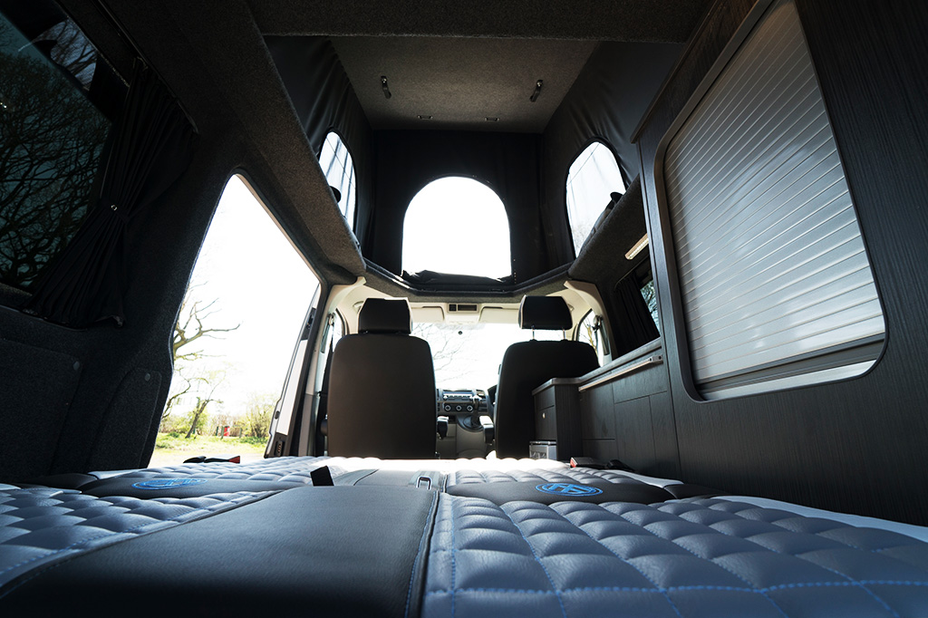 In the rear interior area of the van with view of the bed area